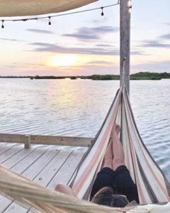 Femme dans un hamac au bord de l'eau instagram